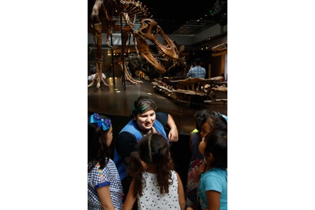 A museum volunteer talking to a group of children in the Dinosaur Hall