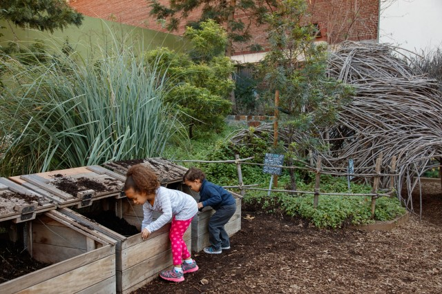 Girl and boy play with dirt in the Nature Gardens compost bins