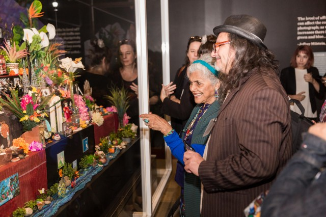 Older woman and man in hat looking intently at a colorful altar in Becoming Los Angeles exhibition