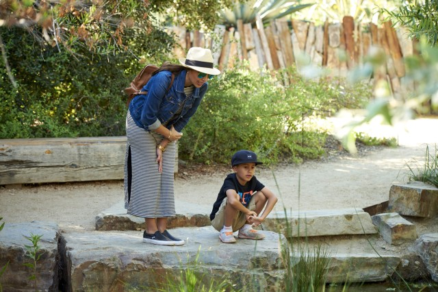 A woman in a sun hat and a boy in a baseball hat by the side of the pond