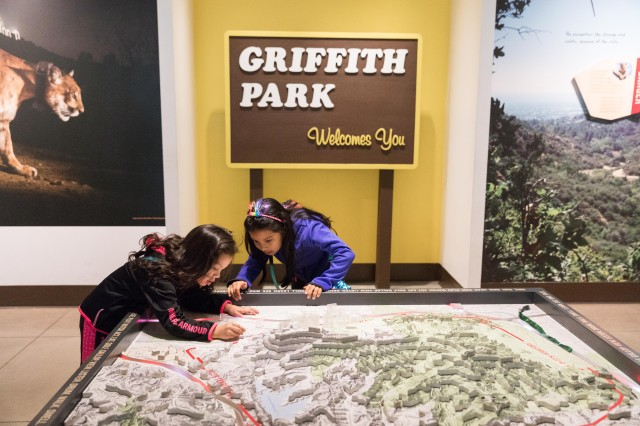 Two girls near Griffith Park sign looking at map in P-22 exhibition