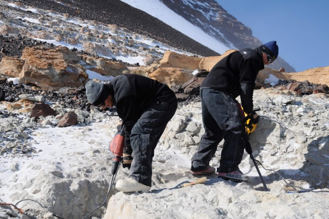 two scientists dig for fossils on mt. kirkpatrick in antarctica