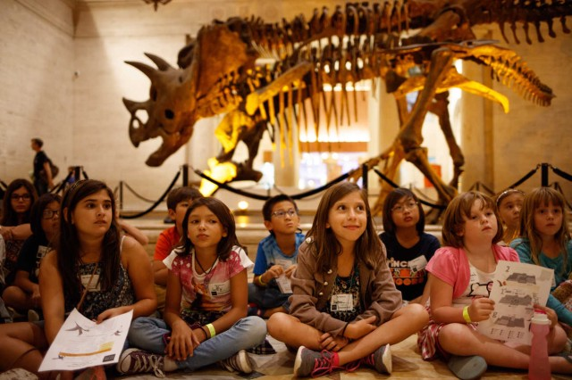 Kids sit in front of Dueling Dinos.