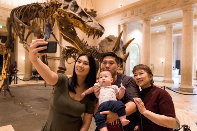 Family takes selfie in front of Dueling Dinos