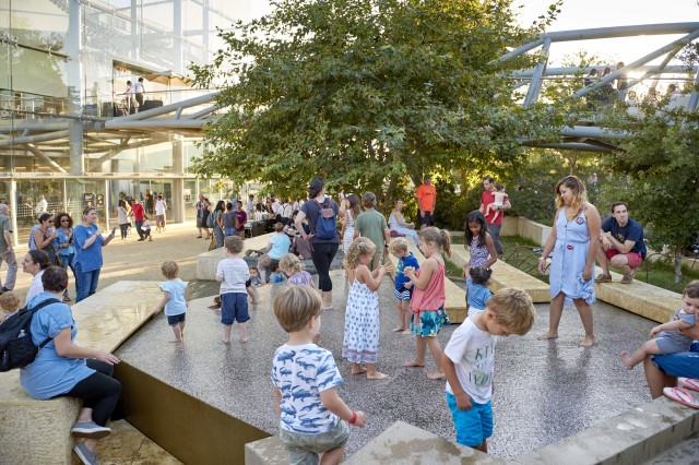 Kids flock to wade in the urban waterfall on a hot summer day
