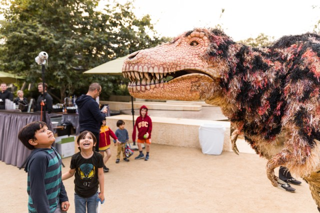 Children admiring a performance of Hunter the dinosaur in NHM Nature Gardens during June First Fridays
