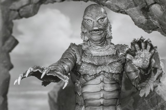 The Creature from the Black Lagoon, a fish like man, reached with his outstretched webbed fingers.