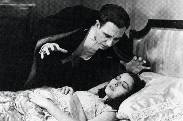 Dracula the vampire leans over a woman sleeping in a bed