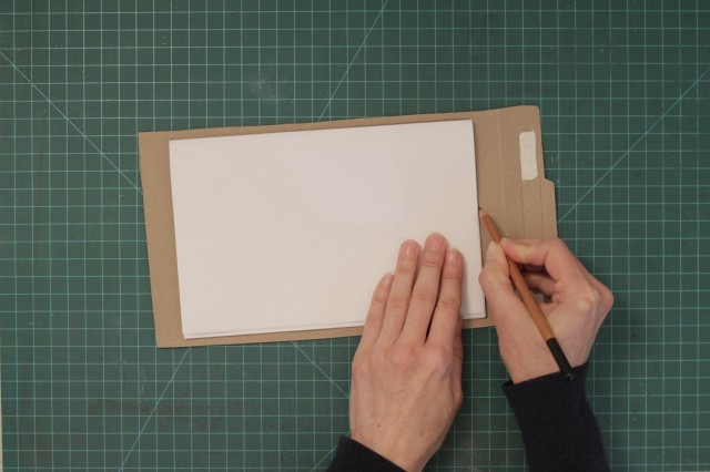 Placing paper on one of the cardboard pieces and tracing the contour of the pages