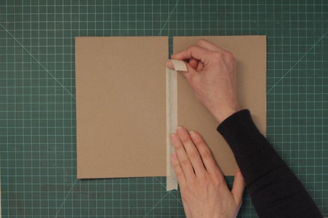 Use a piece of masking tape to connect the two pieces of cardboard leaving about a half inch in between them