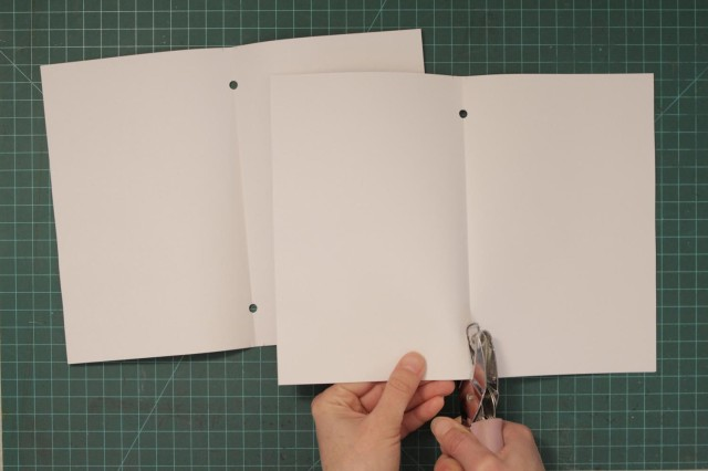 Punch corresponding holes on the folded blank sheets of paper