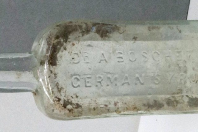 "Antique greenish glass bottle, partially encrusted with dirt, with a raised inscription reading ""Dr A Boschee German Syrup"""