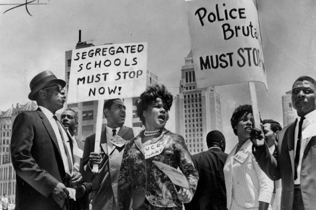 Black and white photo of protesters holding signs