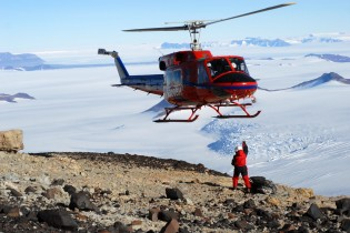 helicopter flying over person in antarctica