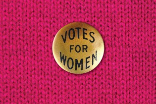 Votes for Women pin against pink background