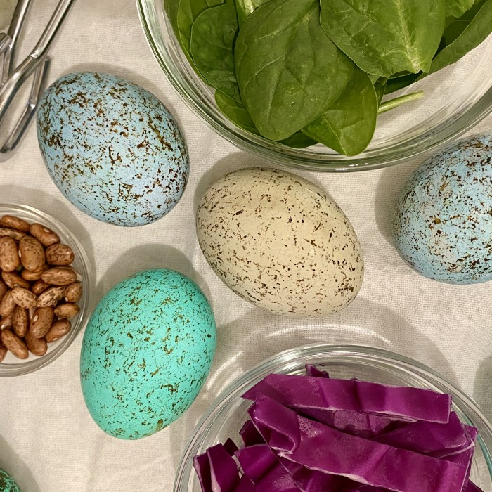 4 speckled eggs on a table surrounded by spinach, nuts, and cabbage