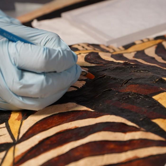 Hand working on tapa restoration