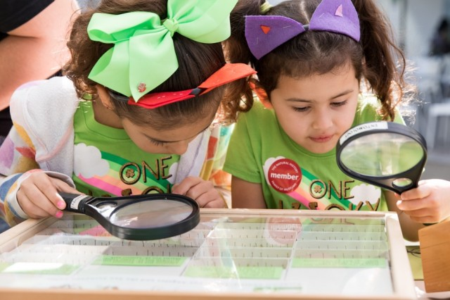 Photograph of kids using magnifying glasses to look at NHM collection items