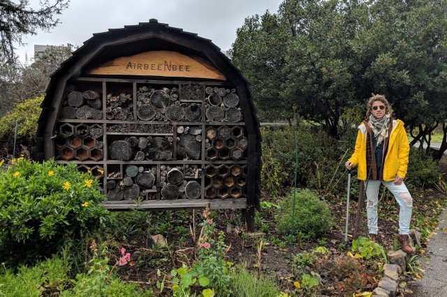 Kat Superfisky stands next to a bee hotel