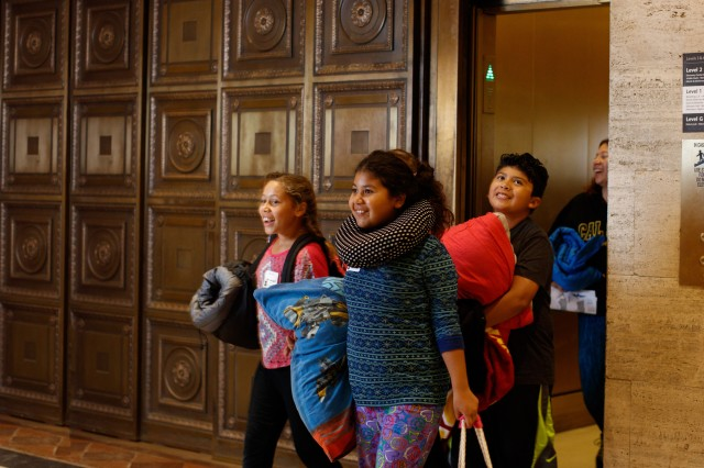 Group of kids at sleepover stepping out of elevator