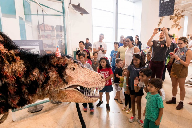 Image of dinosaur puppet with museum visitors