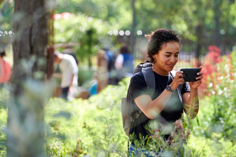 girl taking picture with phone in nature gardens