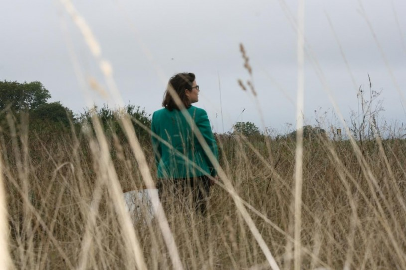 Emily Hartop stands in tall grass holding a butterfly net