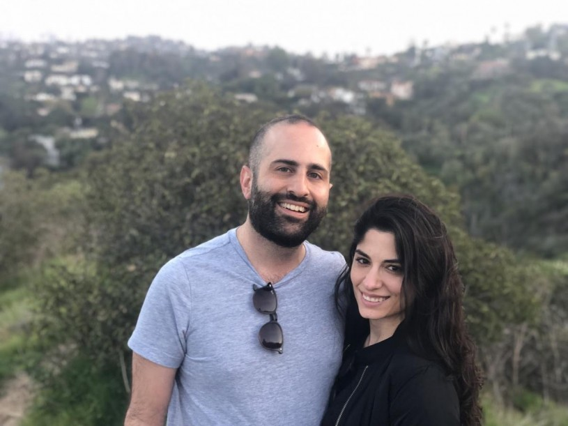 A smiling couple facing the camera stand in nature with a view of the city in the background