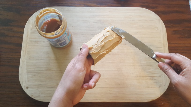 Image of bird feeder step 2 - spreading peanut butter on paper roll