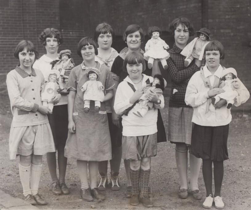 """Group of girls holding """"blue-eyed' dolls"""