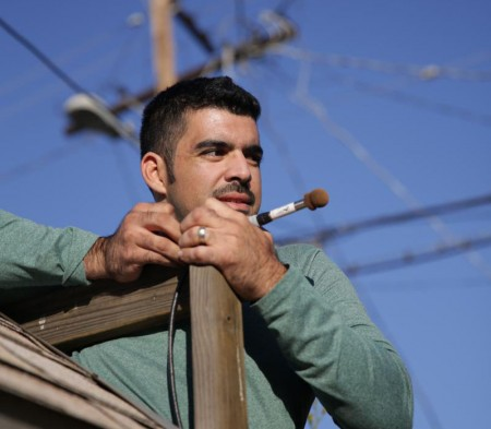 Miguel setting up a bat detector on a children's play structure in a South L.A. backyard.